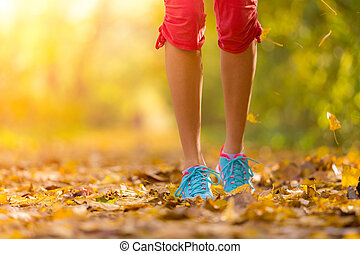 Close up of feet of a runner running in leaves - Close up of...