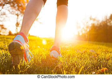 Close up of feet of a runner running in grass - Close up of...