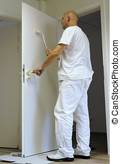 Craftsmen during the painting of a door in an office...