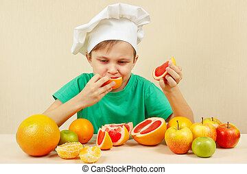 Little boy in chefs hat eat fresh acidic grapefruit at table...