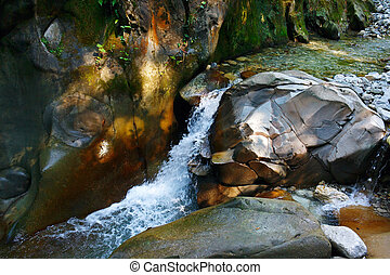 Little wondrous waterfall among the rocks in mountain forest...