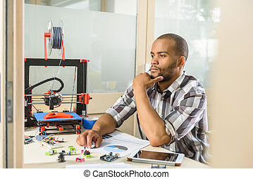 Thoughtful young man engineering 3d printer - Pensive young...