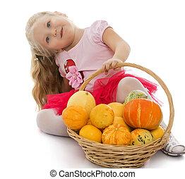 Girl holding a pumpkin - Gute little girl next to a basket...