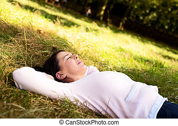 lying in the park - young woman lying in the park relaxing