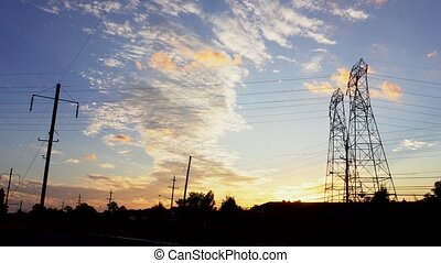 Silhouette electricity pylons in sunset background - ULTRA...