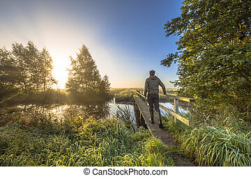 Man crossing bridge to other side with bright light -...