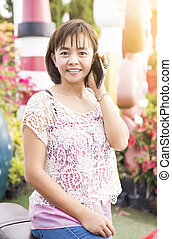 attractive mature Asian woman phoning at home in garden -...