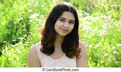 Young girl shyly looking at camera outdoors