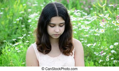The young dark-haired girl looking at camera outdoors