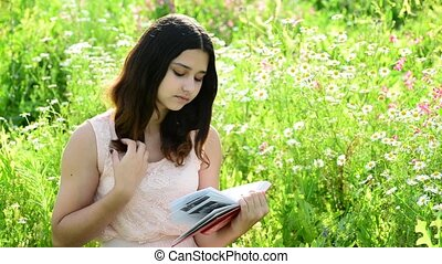 dark-haired girl reading a book on nature