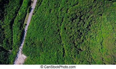 Aerial summer view with the forest, highway, cars, trucks in a mountains