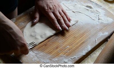 Housewife making chebureks from dough and sausage meat