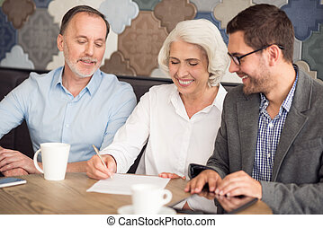 Positive couple cooperating with sales manager - Sign it...