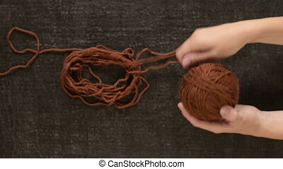 Clewing the brown yarn up - Female hands clewing the brown...
