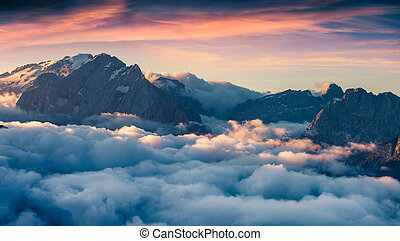 Foggy morning scene in the Val di Fassa valley. View from...
