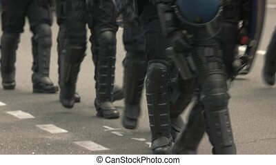 Riot police walking on road. Squad of policemen in armor....