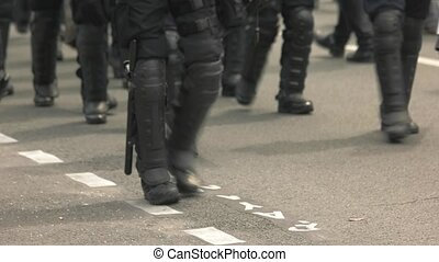 Squad of riot police. Policemen walk on road. Unrest in the...