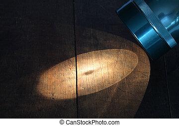 Flashlight - Closeup of luminous flashlight on wooden...