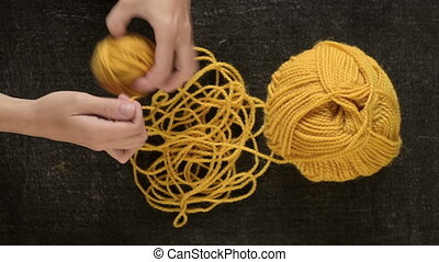 Clewing the yellow yarn up - Female hands clewing the yellow...