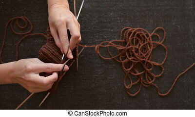Female hands knitting brown yarn on a grunge black...