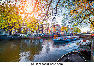 Spring scene in Amsterdam city. Tours by boat on the famous...