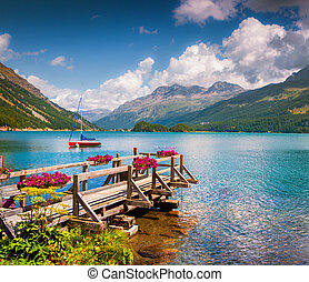 Summer sunny scene on the Silsersee lake with yacht and...