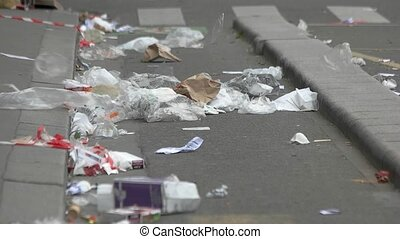 Trash in the street. Wind blowing on garbage. Who turns town...