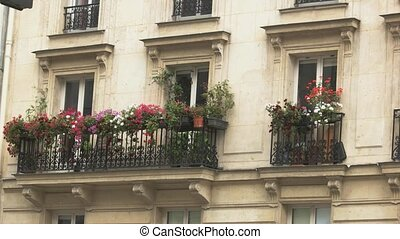Building of beige color. Balconies with flowers. Take a rest...