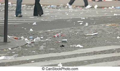 People walk on the road. Trash on the street. City must be...