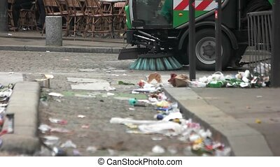 Car cleans the road. Trash on street of town. Improve...