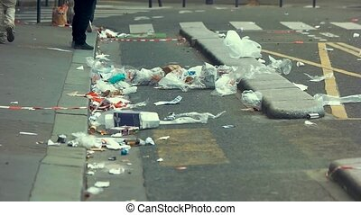 Garbage lying on the street. Legs walk in slow-mo. Pay...