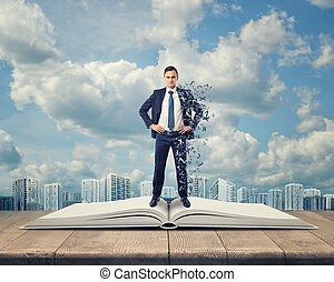 Businessman standing on an open book with letters covering...