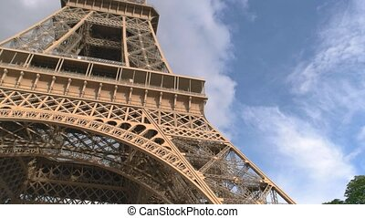 Eiffel tower and cloudy sky. View of monument from below....