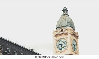 Clock tower at daytime. Classic building with flags. Passage...