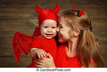 Family mother and baby son celebrate Halloween in devil...