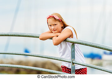 Outdoor portrait of a cute 9 year old girl on a bridge at a...
