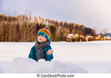 Adorable little boy having fun outdoors on a very cold day,...