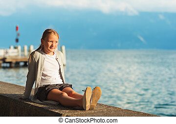 Cute little girl resting by lake Geneva at sunset