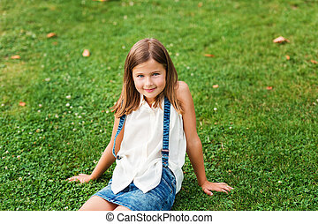 Portrait of a cute little girl 7-8 year old in the park,...