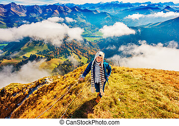 Portrait of a cute little girl in mountains, wearing funny...