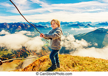 Portrait of a cute little boy in mountains, wearing grey jacket and mountain boots, Moleson-sur-Gruyeres, canton of Fribourg, Switzerland