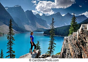 Woman looking at view of lake and mountains.