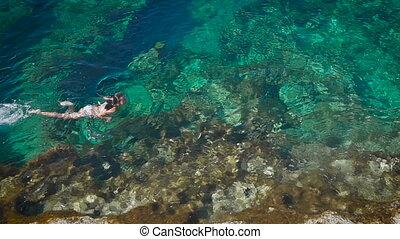 Young woman swimming in beautiful azure sea in Cyprus....