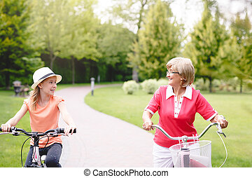 Active senior woman riding bike in a park - Happy active...