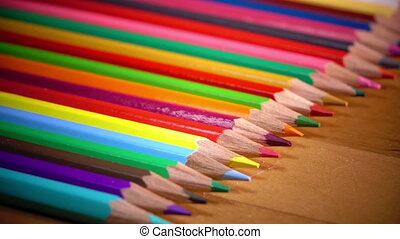 bright color pencils lie in a row on a wooden surface ,