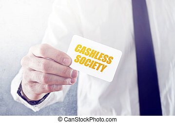 Businessman holding card with Cashless society title,...