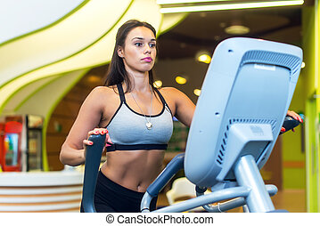 Woman exercising at the gym in an elliptical trainer Cardio...