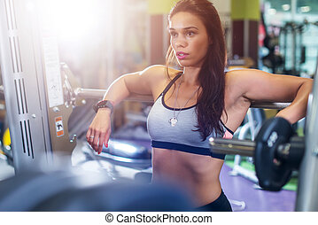 Fit woman in a gym looking at mirror, working with weights....