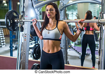 Fit woman doing squats with the barbell Smith machine in the...