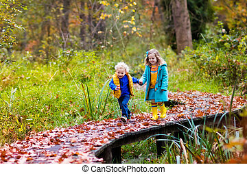 Kids playing in autumn park - Happy children playing in...